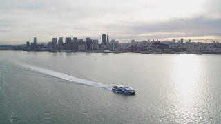 DFKSF06_179 - 5K stock footage aerial video of flying over ferry on the bay, with views of city skyline, Downtown San Francisco, California