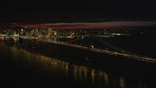 DFKSF07_001 - 5K stock footage aerial video of approaching Bay Bridge with city skyline in distance, San Francisco, California, night