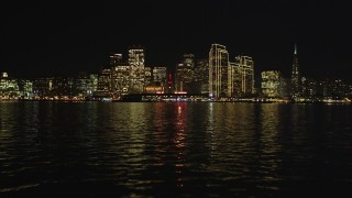 DFKSF07_003 - 5K stock footage aerial video of the city skyline at night seen from the bay, Downtown San Francisco, California, night