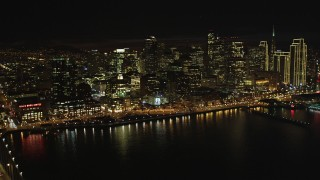 DFKSF07_011 - 5K stock footage aerial video tilt from bay to reveal Bay Bridge and Downtown San Francisco skyscrapers, California, night