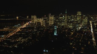 DFKSF07_022 - 5K stock footage aerial video of Coit Tower and the city's skyscrapers, Downtown San Francisco, California, night