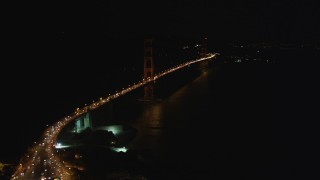 DFKSF07_034 - 5K stock footage aerial video tilt from bird's eye of freeway interchange to reveal Golden Gate Bridge, San Francisco, California, night