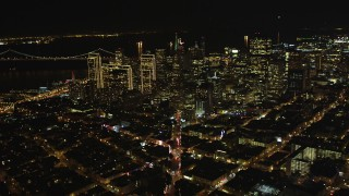 DFKSF07_058 - 5K stock footage aerial video of tilting from Columbus Ave to reveal skyscrapers in Downtown San Francisco, California, night