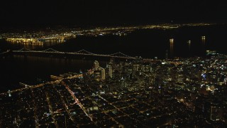 DFKSF07_063 - 5K stock footage aerial video of a high altitude view of Bay Bridge and skyscrapers in Downtown San Francisco, California, night