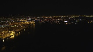 DFKSF07_077 - 5K stock footage aerial video of panning across and approaching the Port of Oakland in California, night