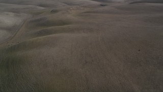 DFKSF08_072 - 5K stock footage aerial video of tilting from brown hills revealing Shiloh Wind Power Plant, Montezuma Hills, California