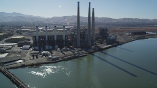 DFKSF08_099 - 5K stock footage aerial video tilt from piers to reveal a power plant with smoke stacks in Pittsburg, California