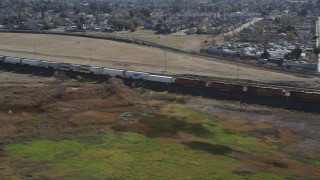 DFKSF08_103 - 5K stock footage aerial video of flying by a train traveling past residential neighborhoods, Pittsburg, California