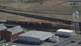DFKSF08_110 - 5K stock footage aerial video of a train passing industrial buildings, Bay Point, California