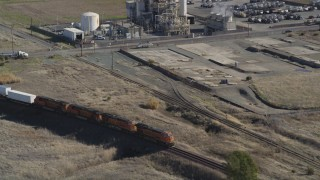 DFKSF08_111 - 5K stock footage aerial video track a train passing by industrial buildings, Bay Point, California