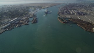DFKSF09_017 - 5K stock footage aerial video of tilting from Oakland Inner Harbor revealing cargo ship in Port of Oakland, California