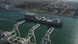 DFKSF09_020 - 5K stock footage aerial video of a reverse view of a cargo ship passing cargo cranes in the Port of Oakland, California