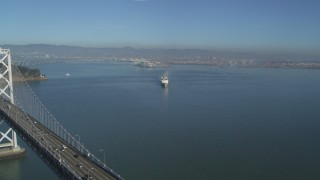 DFKSF09_045 - 5K stock footage aerial video fly over the Bay Bridge to reveal a cargo ship, San Francisco, California