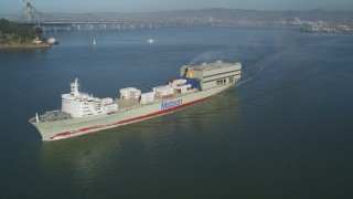 DFKSF09_046 - 5K stock footage aerial video of tracking a passing cargo ship to reveal the Bay Bridge, San Francisco, California