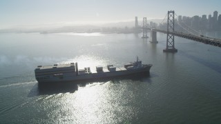 DFKSF09_048 - 5K stock footage aerial video track a cargo ship approaching the Bay Bridge, San Francisco, California