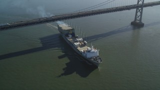 DFKSF09_050 - 5K stock footage aerial video fly away from a cargo ship sailing under the Bay Bridge, San Francisco, California