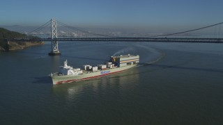 DFKSF09_051 - 5K stock footage aerial video track a cargo ship sailing away from the Bay Bridge, San Francisco, California