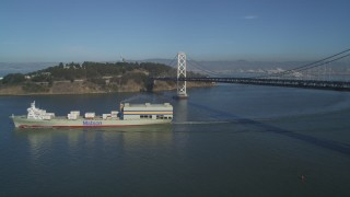DFKSF09_052 - 5K stock footage aerial video of flying by a cargo ship sailing away from the Bay Bridge, San Francisco, California