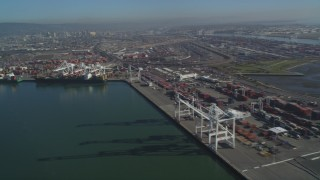 DFKSF09_056 - 5K stock footage aerial video pan across the Port of Oakland to approach cargo cranes, California