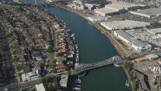 DFKSF09_061 - 5K stock footage aerial video of suburban homes in Alameda and warehouse buildings across the estuary in Oakland, California