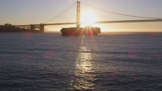 DFKSF10_021 - 5K stock footage aerial video of a cargo ship near Golden Gate Bridge, San Francisco, California, sunset