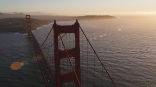 DFKSF10_023 - 5K stock footage aerial video of flying over Golden Gate Bridge, reveal cargo ship, San Francisco, California, sunset