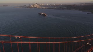 DFKSF10_024 - 5K stock footage aerial video of cargo ship on San Francisco Bay, seen from Golden Gate Bridge, San Francisco, California, sunset