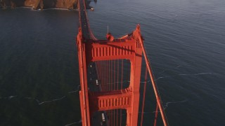 DFKSF10_029 - 5K stock footage aerial video approach tower on the Golden Gate Bridge and tilt to bird's eye of traffic in San Francisco, California, sunset