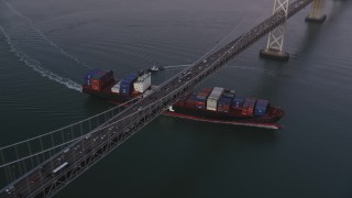 DFKSF10_051 - 5K stock footage aerial video of a cargo ship sailing under Bay Bridge, San Francisco, California, sunset