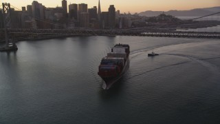 DFKSF10_052 - 5K stock footage aerial video of a cargo ship sailing under Bay Bridge, reveal Downtown San Francisco skyline, California, sunset