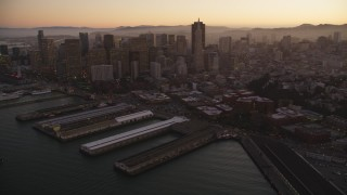 DFKSF10_063 - 5K stock footage aerial video pan from Coit Tower, revealing Downtown San Francisco skyscrapers, California, sunset