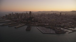 DFKSF10_064 - 5K stock footage aerial video of downtown skyscrapers and Coit Tower, reveal Pier 39, Fisherman's Wharf, San Francisco, California, twilight