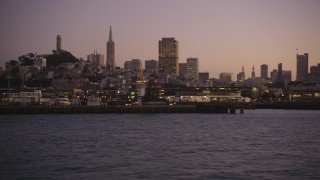 DFKSF10_072 - 5K stock footage aerial video of flying by Fisherman's Wharf, revealing Pier 39, San Francisco, California, twilight