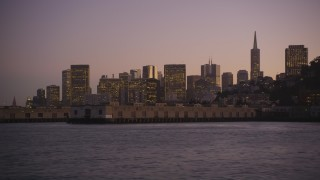 DFKSF10_073 - 5K stock footage aerial video of flying low over the bay by Coit Tower and Downtown San Francisco skyline, California, twilight