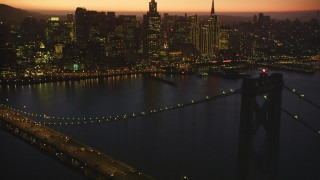 DFKSF10_088 - 5K stock footage aerial video tilt from the Bay Bridge, revealing Downtown San Francisco skyline, California, twilight