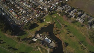 DFKSF11_001 - 5K stock footage aerial video fly away from suburban homes and golf course to reveal Hayward Executive Airport, California