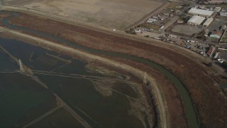 DFKSF11_002 - 5K stock footage aerial video flyby power lines and marshland, reveal water treatment plant, Union City, California