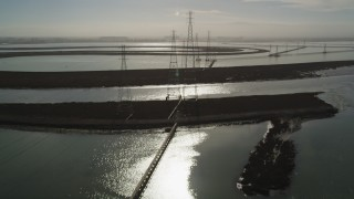 DFKSF11_010 - 5K stock footage aerial video of flying over power lines through marshlands, Sunnyvale, California