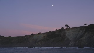 DFKSF14_032 - 5K stock footage aerial video approach and flyby coastal cliffs with the moon above, San Francisco, California, twilight