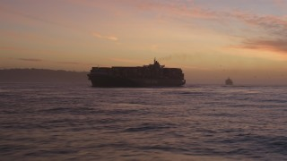 DFKSF14_040 - 5K stock footage aerial video of a cargo ship on the San Francisco Bay in San Francisco, California, twilight