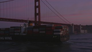 DFKSF14_041 - 5K stock footage aerial video orbit cargo ship and reveal Golden Gate Bridge, San Francisco, California, twilight