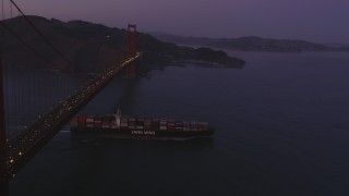 DFKSF14_042 - 5K stock footage aerial video fly over Golden Gate Bridge, reveal cargo ship, San Francisco, California, twilight