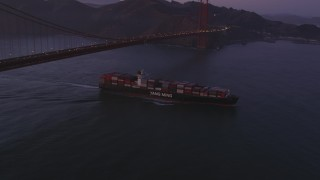 DFKSF14_043 - 5K stock footage aerial video of a cargo ship sailing under Golden Gate Bridge, San Francisco, California, twilight