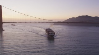 DFKSF14_044 - 5K stock footage aerial video of flying by cargo ship under Golden Gate Bridge, San Francisco, California, twilight