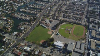 DFKSF15_002 - 5K stock footage aerial video of a reverse view of suburban neighborhoods and baseball fields, Alameda, California