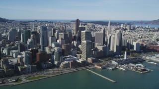 DFKSF15_008 - 5K stock footage aerial video of approaching waterfront skyscrapers and the Ferry Building in Downtown San Francisco, California