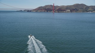 DFKSF15_022 - 5K stock footage aerial video of approaching boat on the bay, tilt to reveal Golden Gate Bridge, San Francisco, California