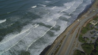 DFKSF15_044 - 5K aerial stock footage video of a reverse view of ocean waves and Great Highway, Lakeshore District, San Francisco, California