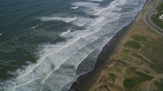 DFKSF15_045 - 5K stock footage aerial video of waves rolling toward coastal cliffs in the Lakeshore District, San Francisco, California