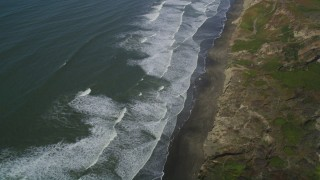 DFKSF15_046 - 5K stock footage aerial video fly away from waves rolling toward beach and cliffs in the Lakeshore District, San Francisco, California